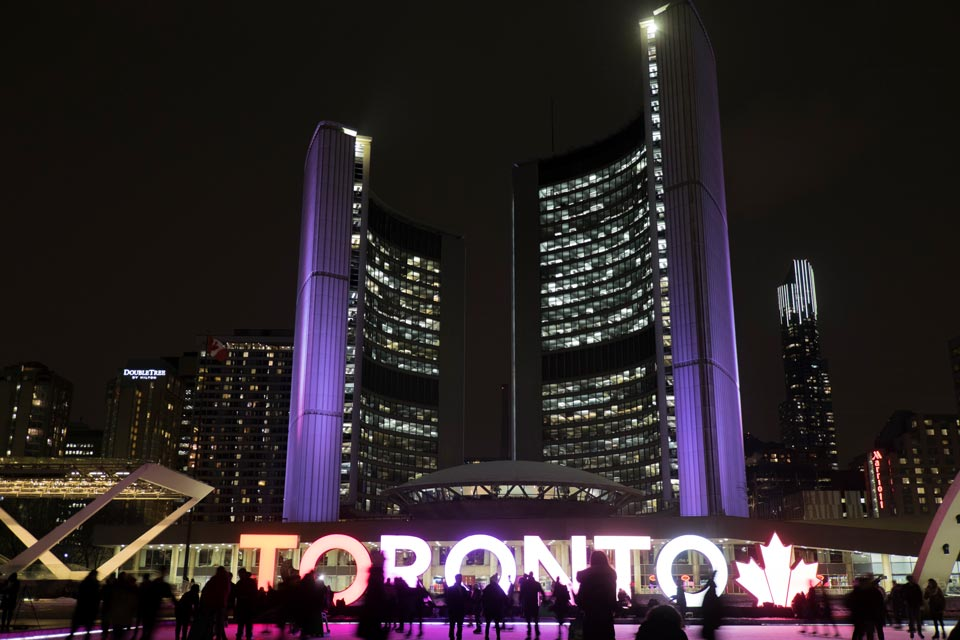 toronto-sign-with-maple-leaf-and-city-hall-night